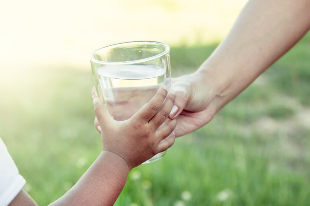 Woman handing a child a glass of water