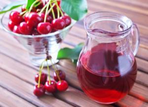 Glass of tart cherry juice and a bowl of tart cherries that can be consumed to help with muscle relaxation.