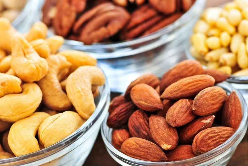Bowls of almonds, cashews, and pecans which are high protein nut sources.